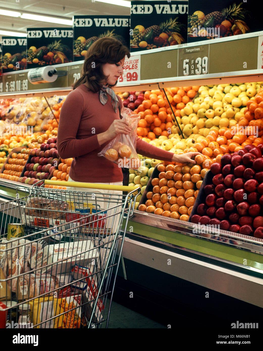 1970 FEMME ÉPICERIE PANIER SÉLECTION D'ORANGES DANS PRODUIRE MINISTÈRE DE L'ALIMENTATION Photo Stock