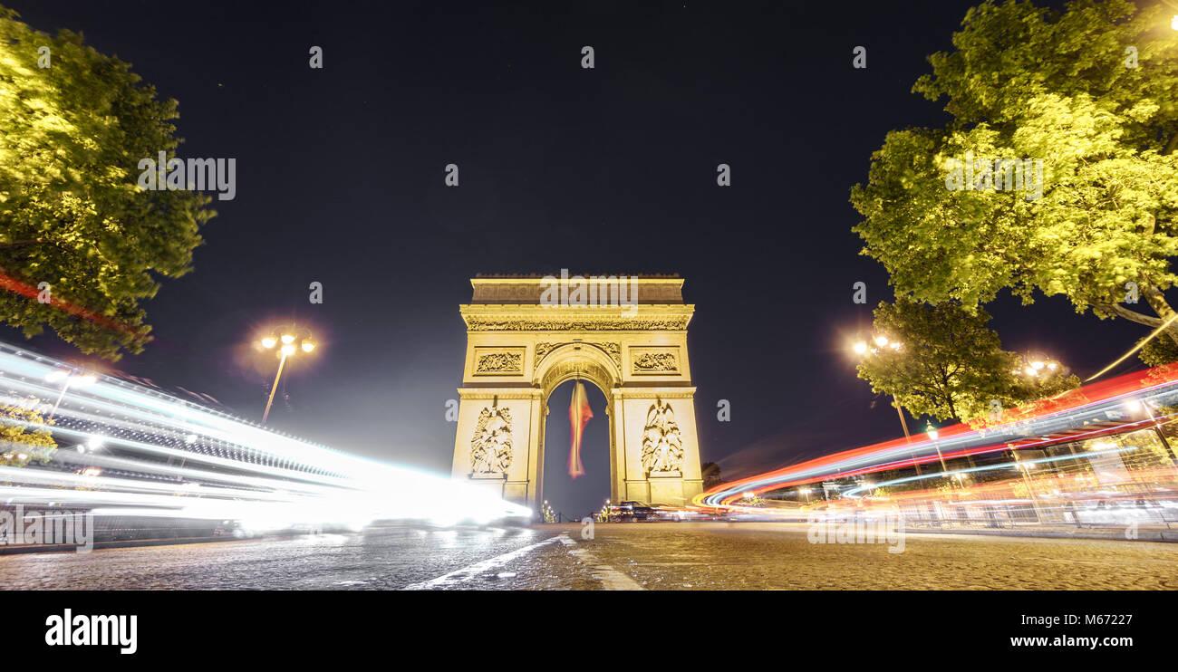 Arc de Triomphe et de light trails de nuit Photo Stock