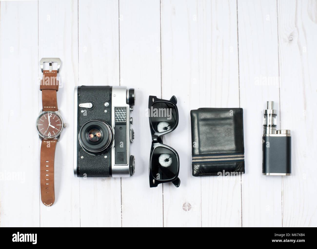 Accessoires pour hommes. Appareil photo, montre, lunettes de soleil sur fond de bois Photo Stock
