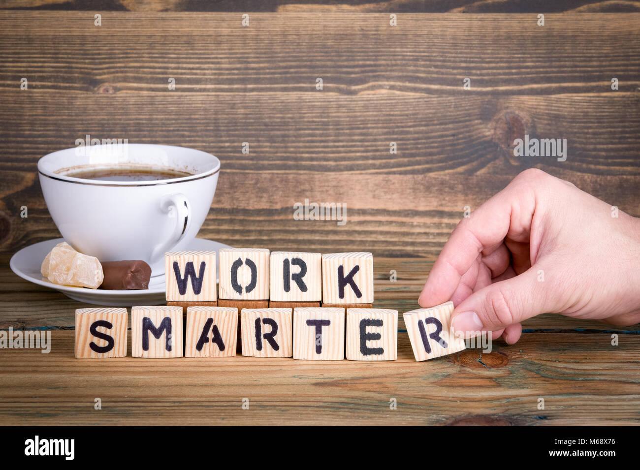 Travailler plus intelligemment. Lettres en bois sur le bureau d'information et de la communication, bureau arrière Photo Stock