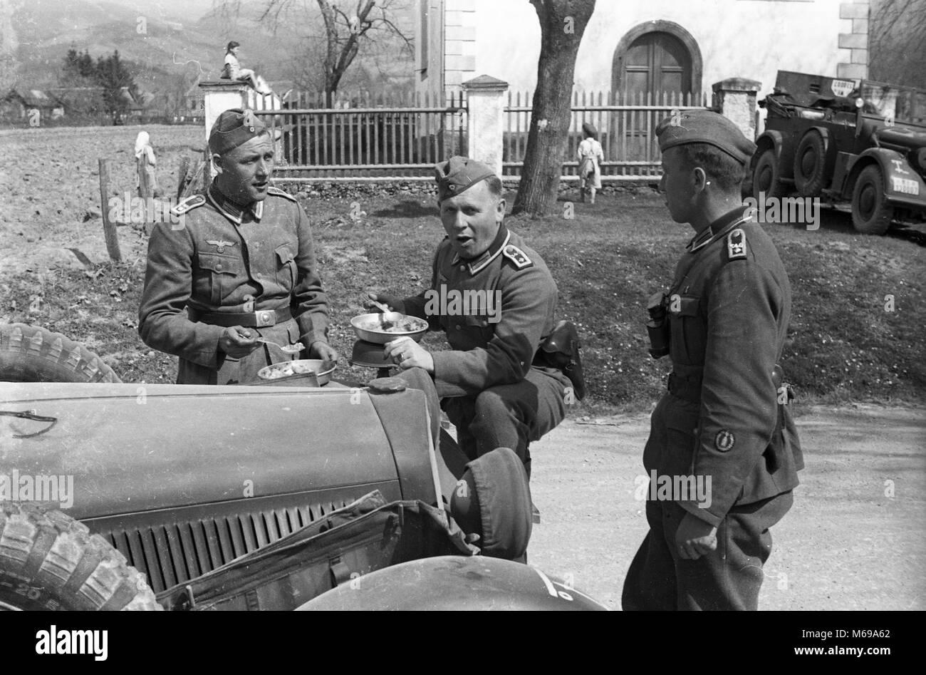 Les soldats de l'armée allemande de manger le déjeuner avec les enfants jouant dans l'arrière-plan lors de l'invasion de la Yougoslavie en avril 1941. Banque D'Images