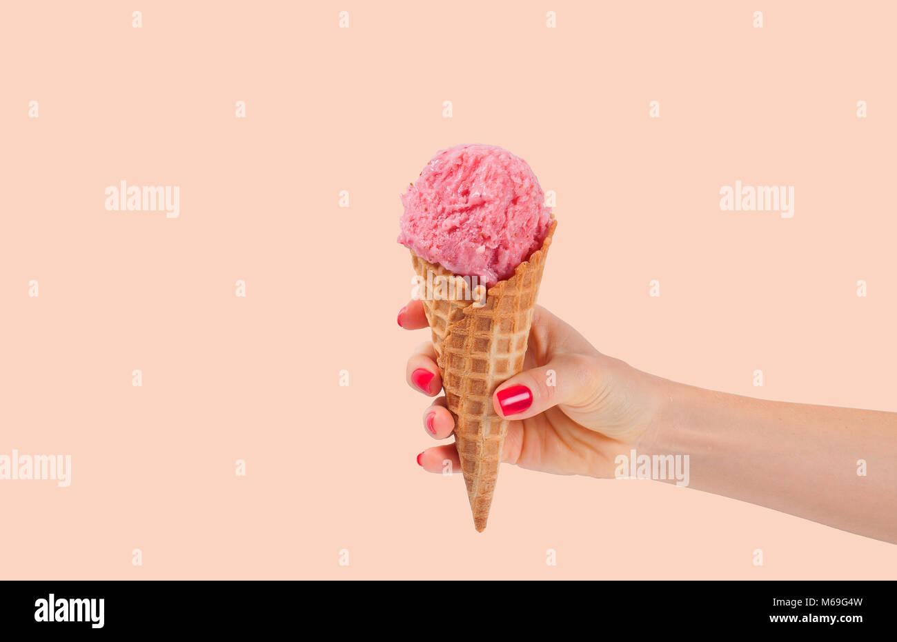 Hand holding strawberry ice cream cone sur fond de couleur pastel délavées. Glace à la fraise en Photo Stock