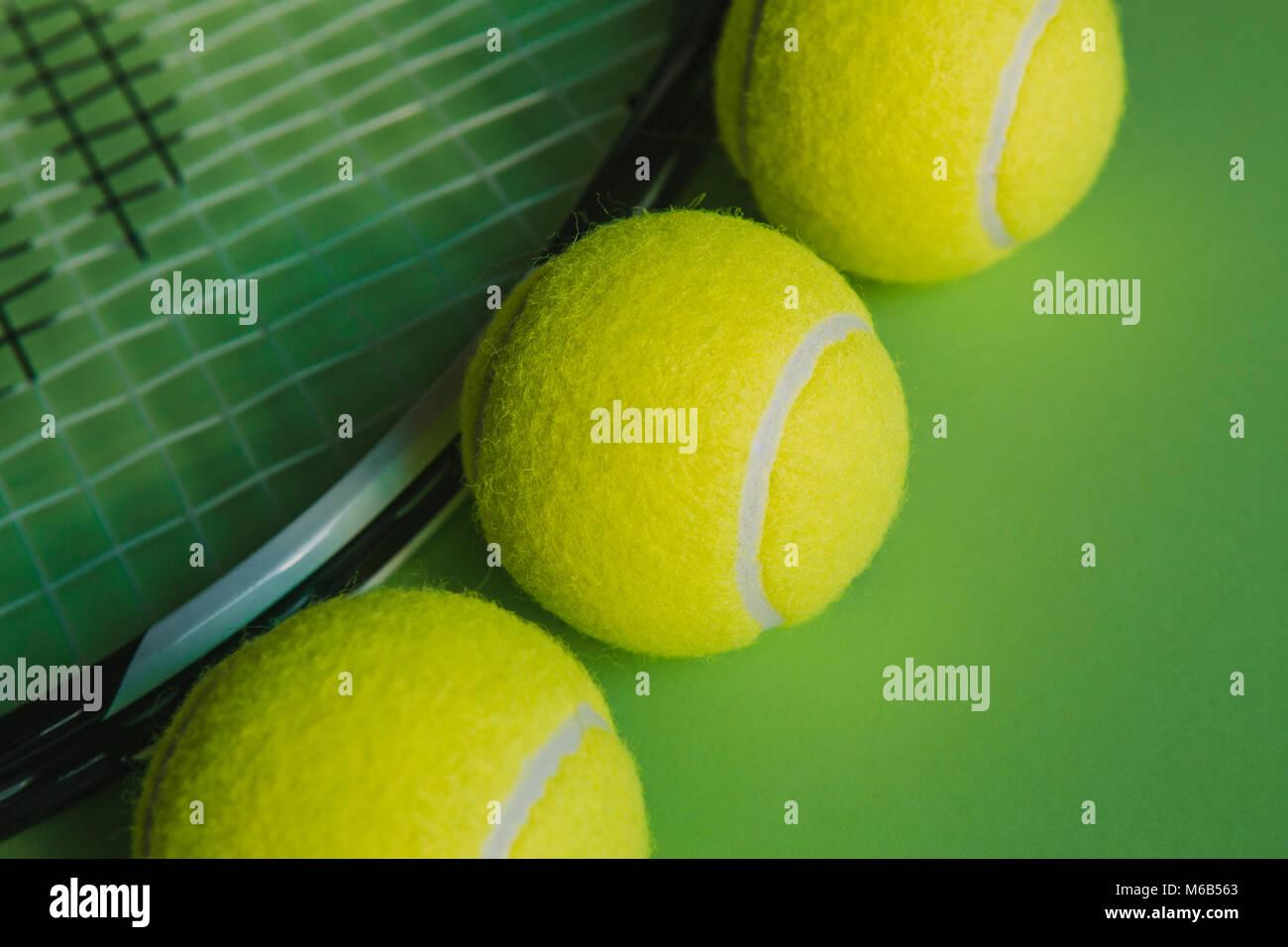 3094751abce3a Macro-vision de 3 balles de tennis et une raquette de tennis sur fond vert.