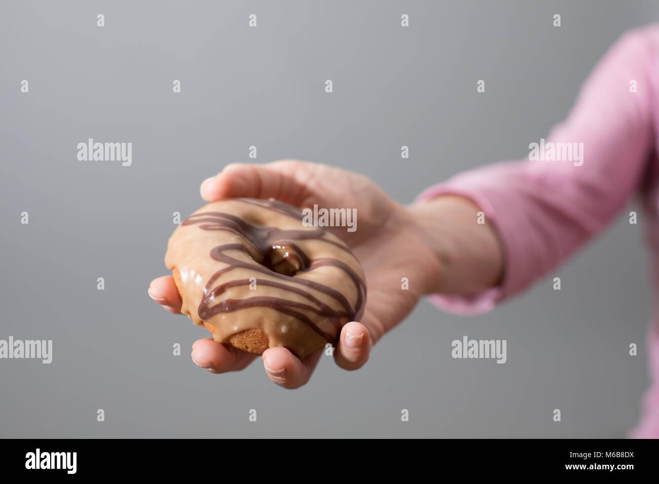 Une main féminine offrant un beigne sur un fond gris transparent Photo Stock