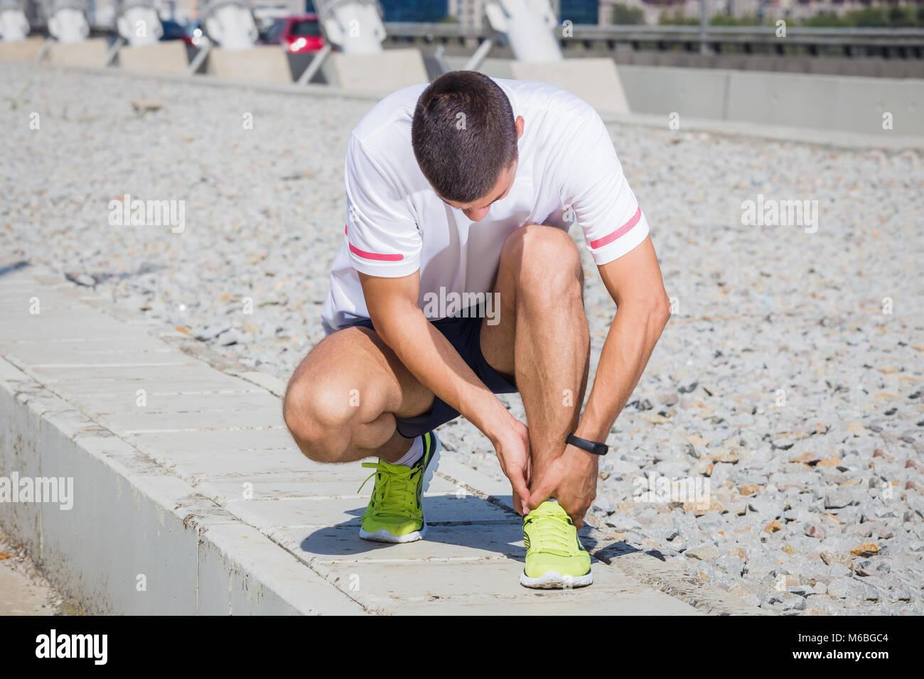 L'athlète exécute la sensation de douleur après avoir son genou blessé. Accident sur une piste de course au cours Banque D'Images