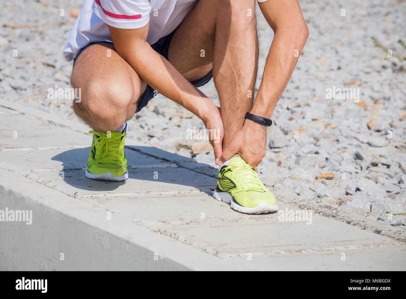 L'athlète exécute la sensation de douleur après avoir sa jambe blessée. Accident sur une piste de course au cours Banque D'Images