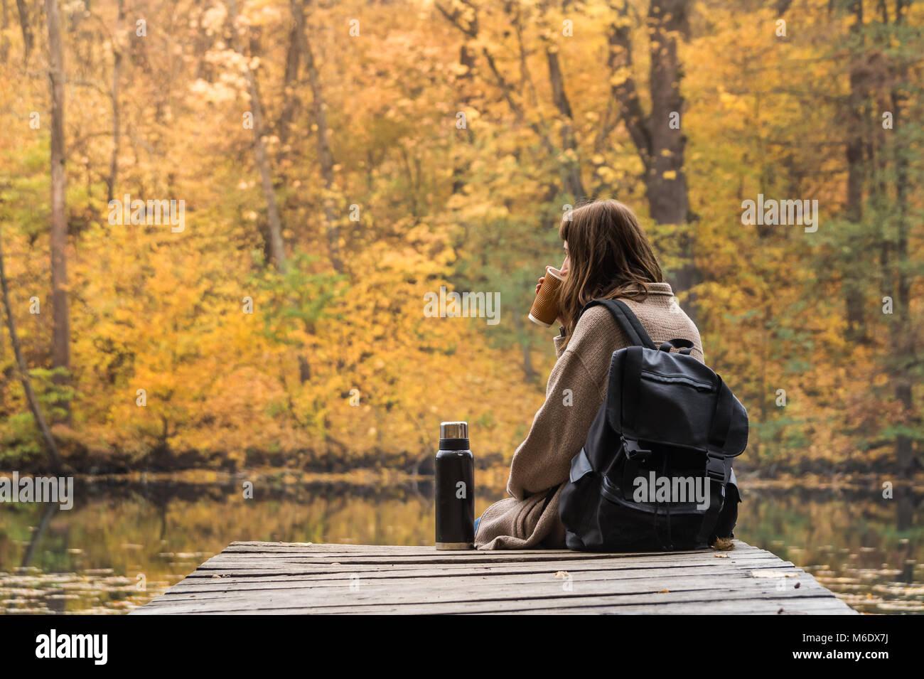 Girl reste et boisson chaude de thermos près du lac dans un parc de la nature sur un jour d'automne d'or Photo Stock