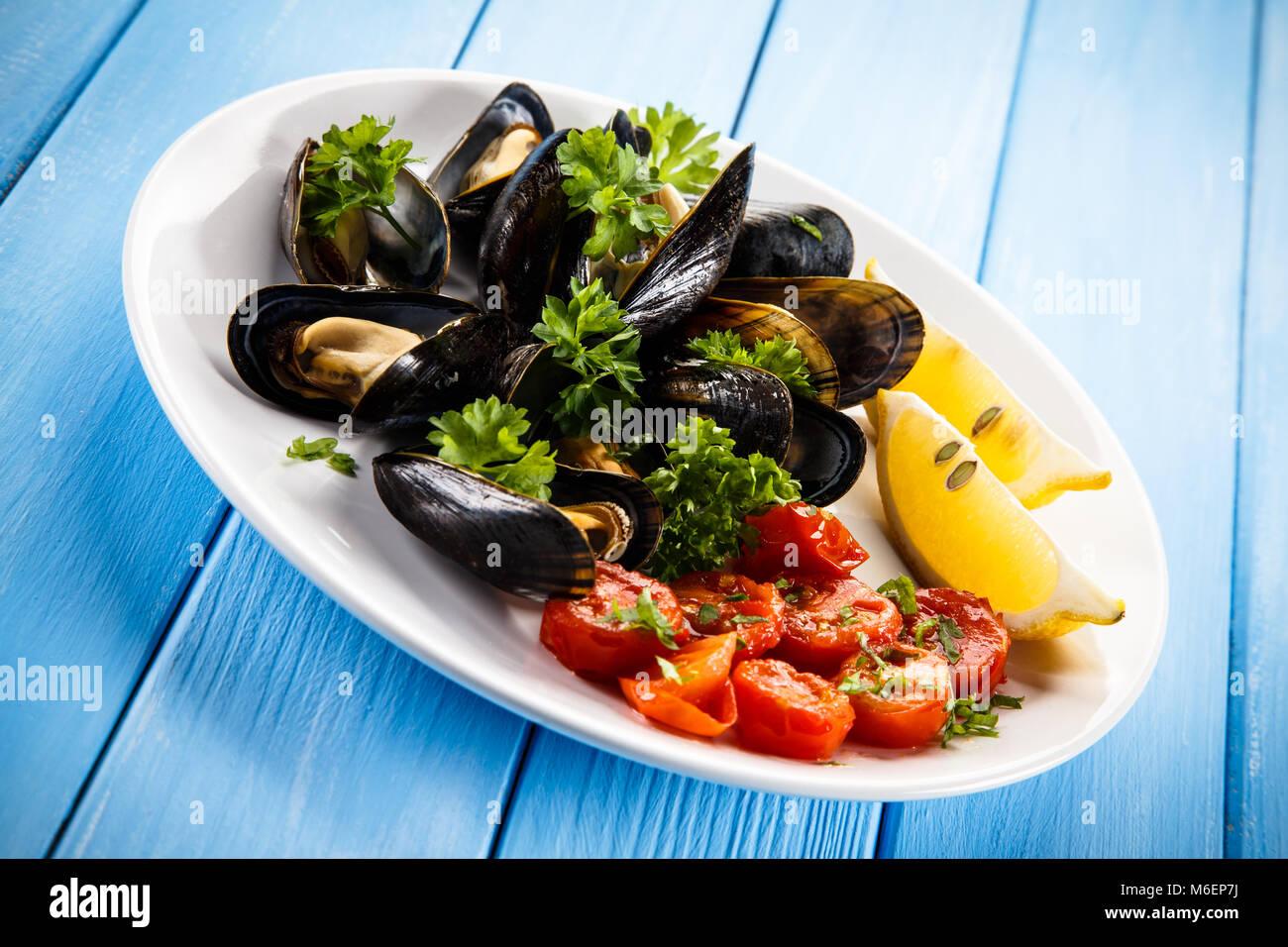 Moules cuites avec du citron et des tomates cerises Photo Stock