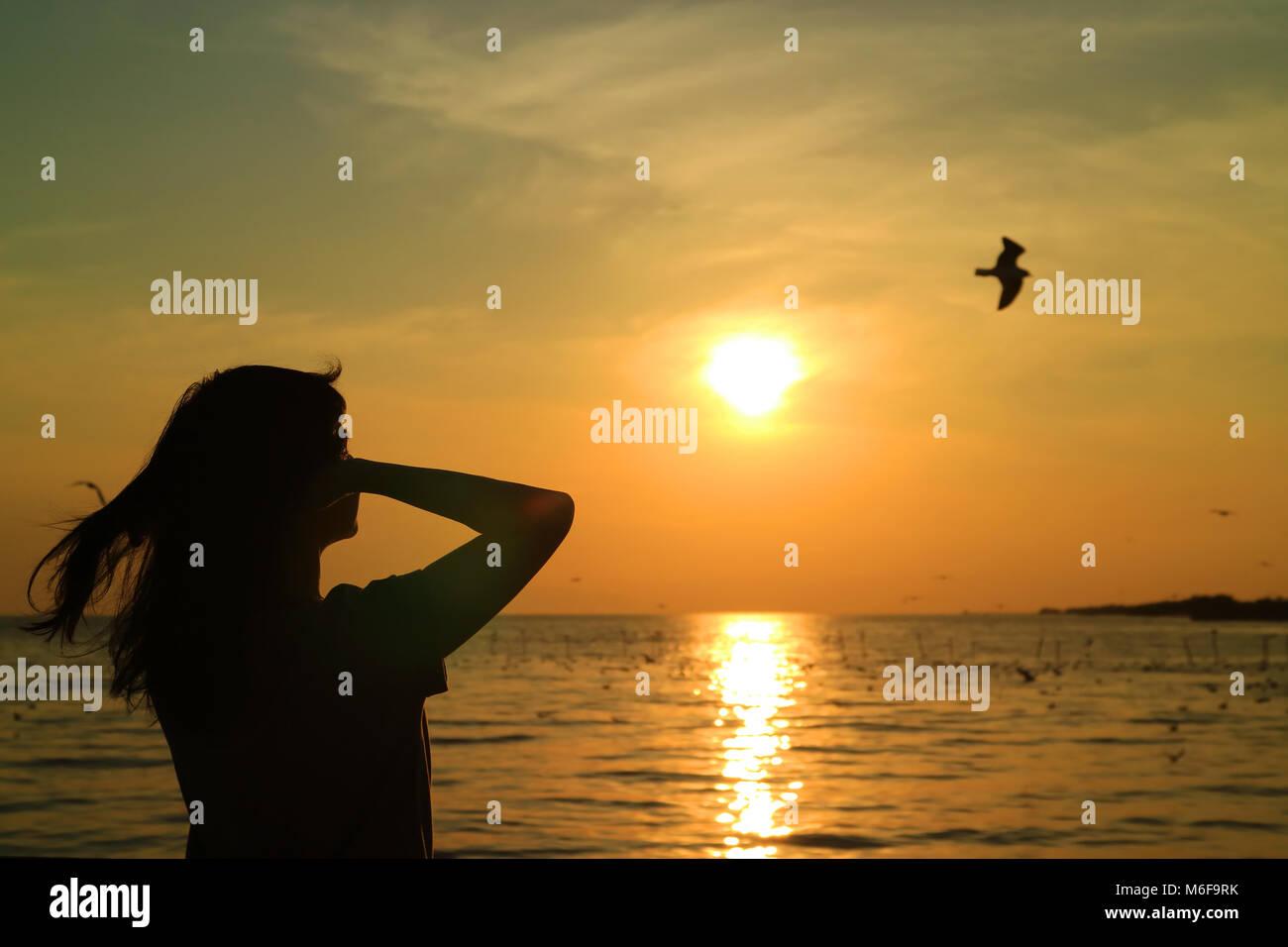 Silhouette de jeune femme regardant le soleil se lever sur golden sky avec un oiseau volant Photo Stock