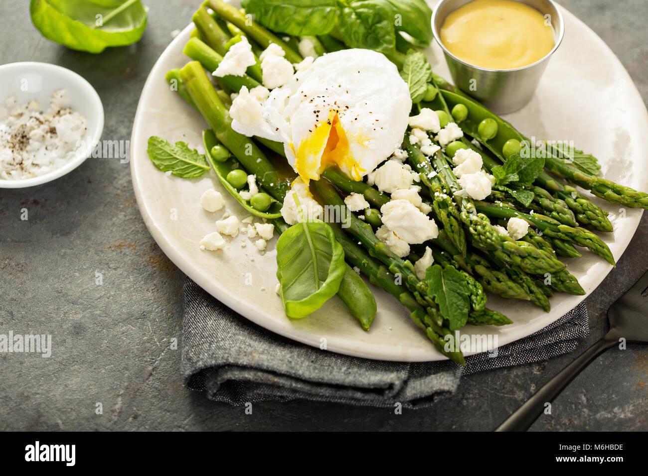 Les petits pois et les asperges avec œuf poché Photo Stock