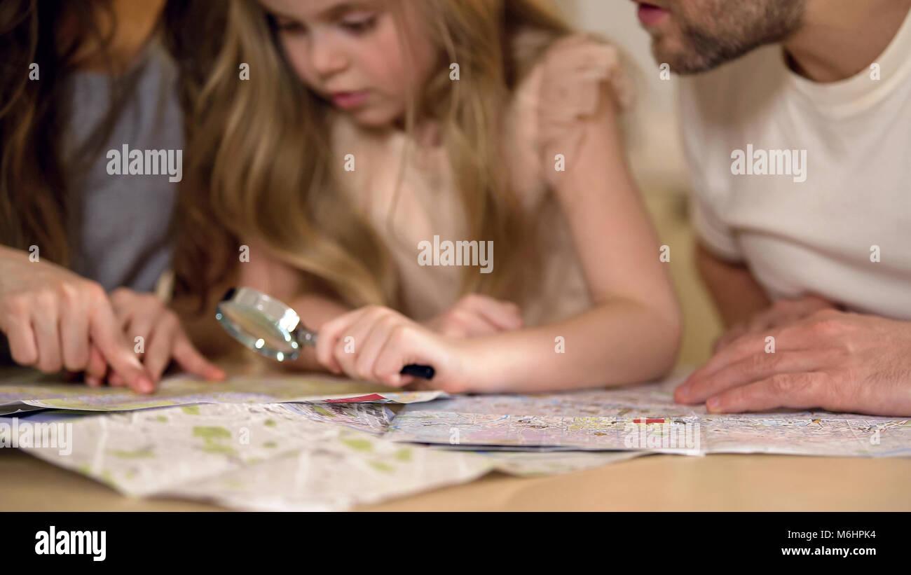 Petite fille curieuse affichage de carte du monde, de concert avec les parents, la planification locations Photo Stock