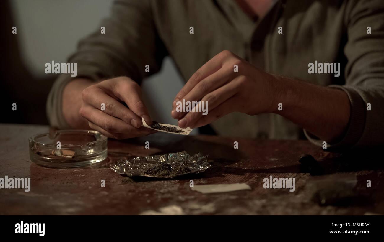 Jeune homme faire de cigarette de cannabis pour soulager le stress, l'abus de substances psychoactives Banque D'Images