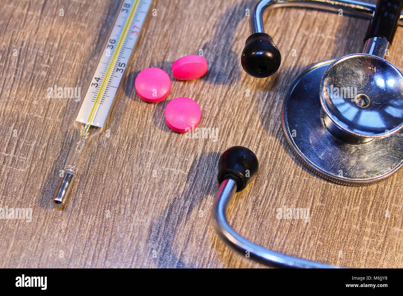 Stéthoscope, comprimé et thermomètre close up, concept médical Banque D'Images