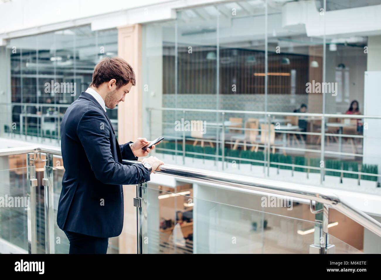 Businessman with smartphone via office building Photo Stock