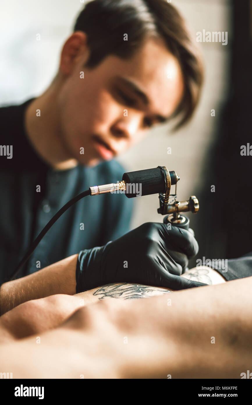 Artiste masculin de tatouage fait un tatouage sur la jambe d'une femme. Photo Stock