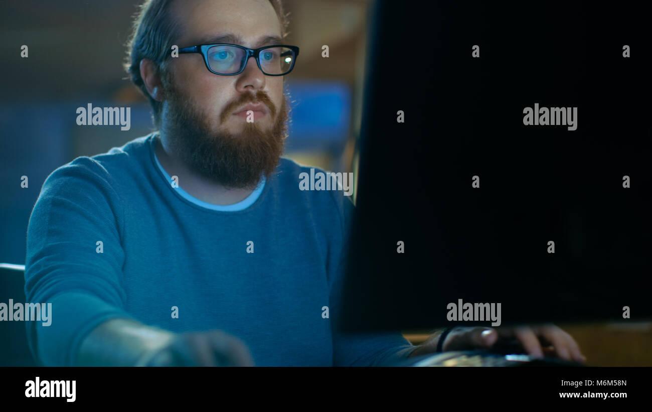 L'accent jeune homme travaille sur un ordinateur personnel. Il porte des lunettes et a Barbe, il travaille tard Photo Stock