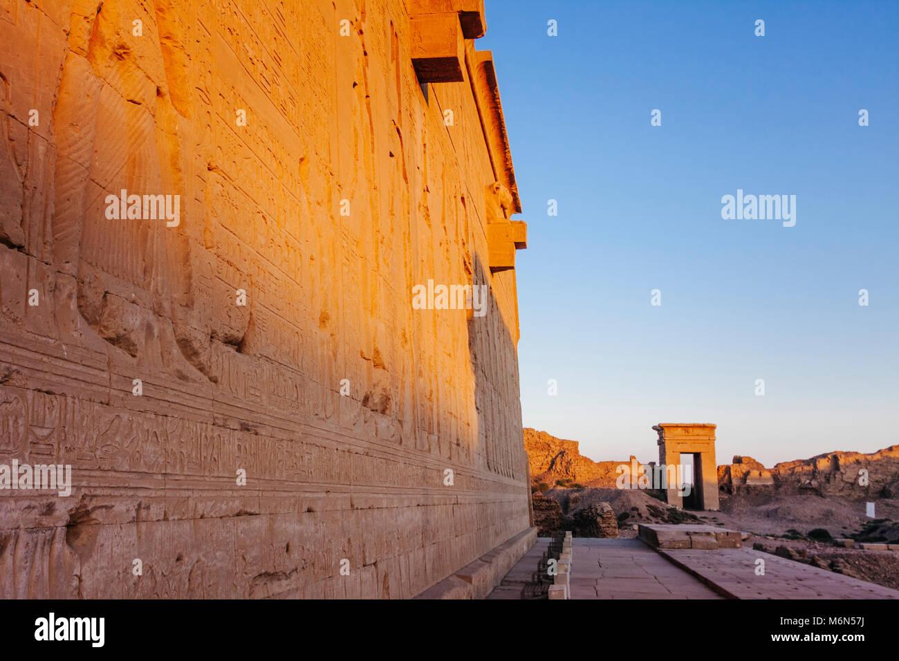 Bas-reliefs en dehors du Temple d'Hathor avec l'une des passerelles du composé en arrière-plan au coucher du soleil. Banque D'Images