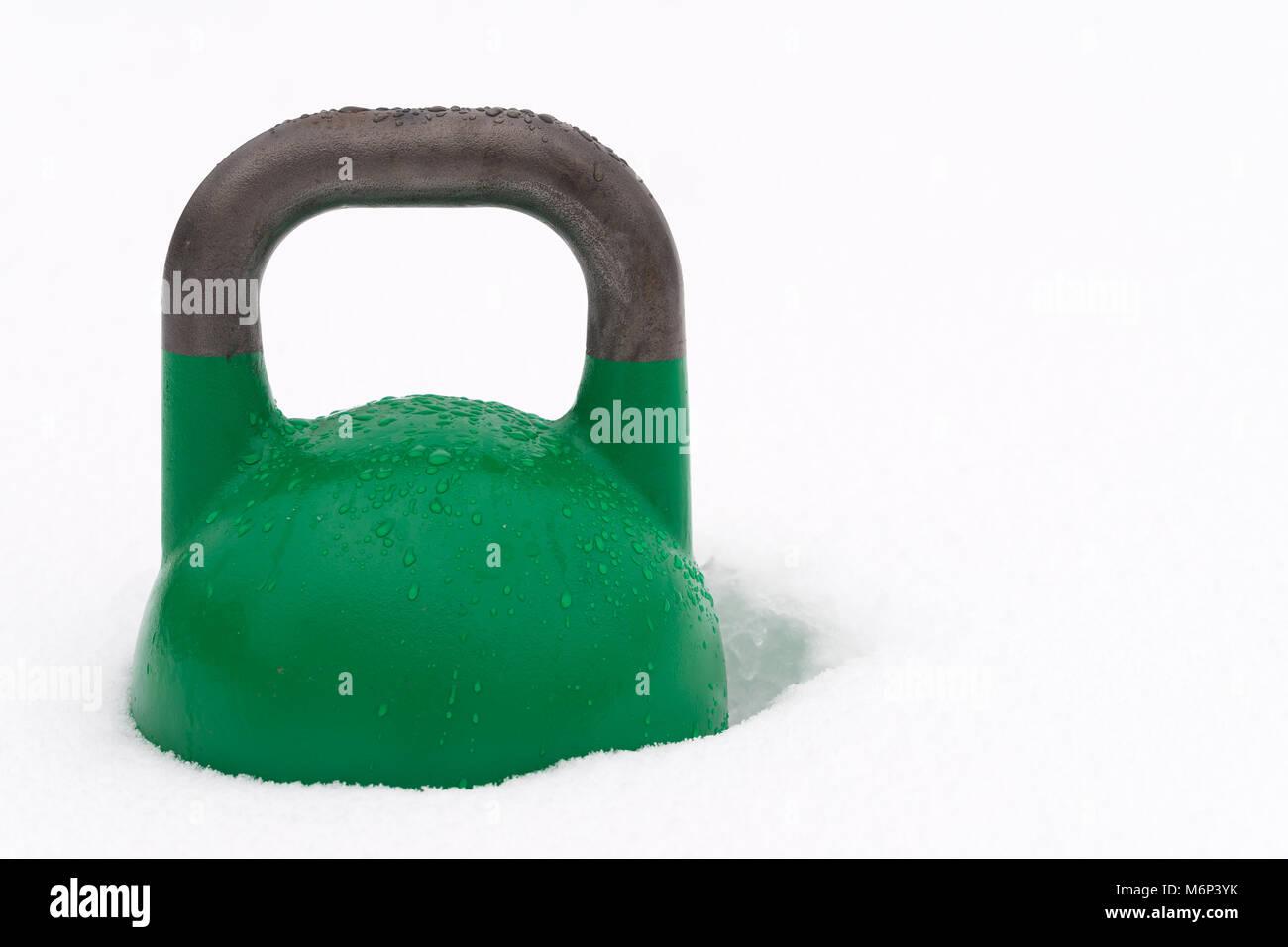 Poids kettlebell formation verte couverte de gouttelettes d'eau à l'extérieur dans la neige. Copie Photo Stock