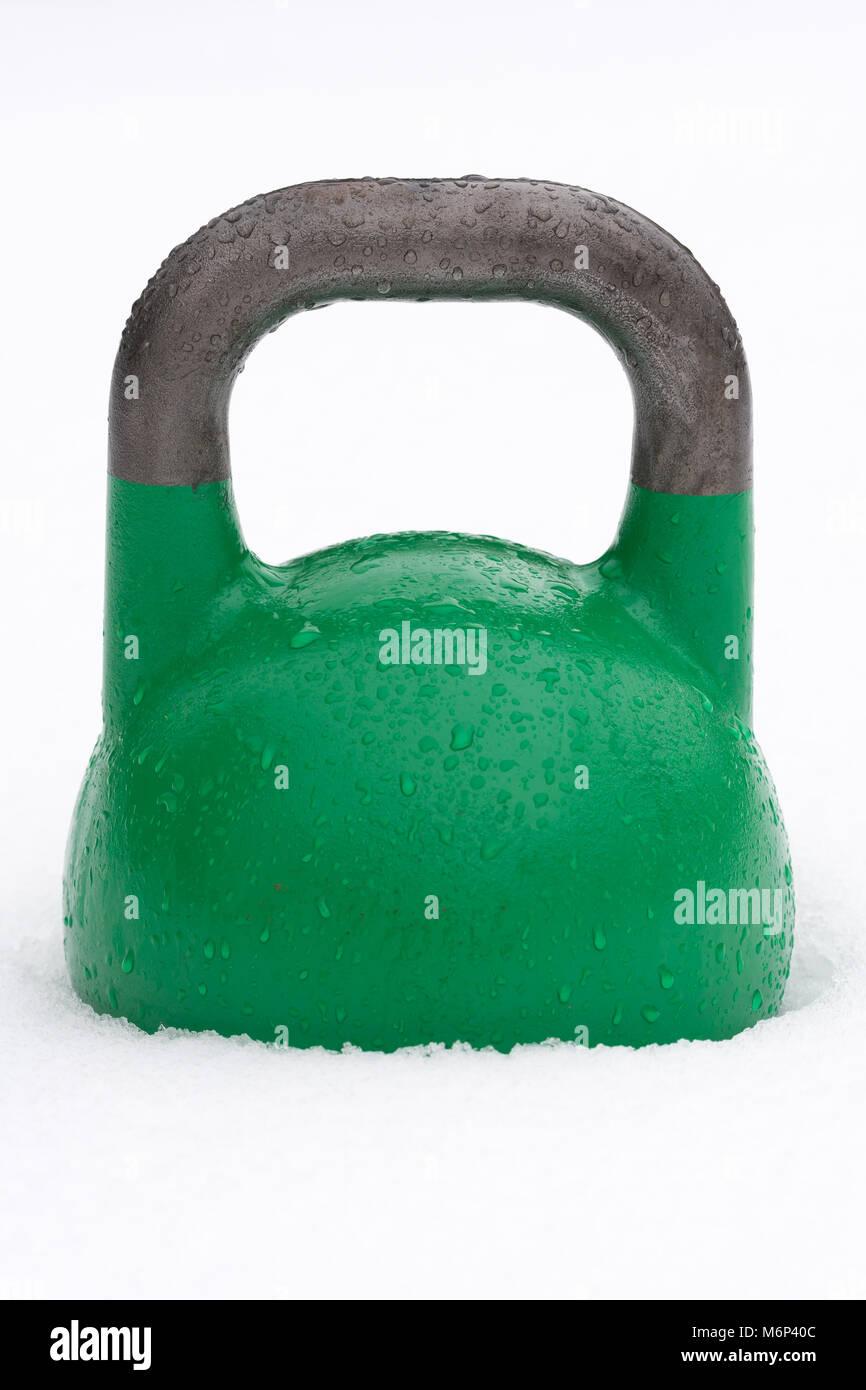 Poids kettlebell formation vert à l'extérieur dans la neige. La concurrence verte kettlebells peser Photo Stock