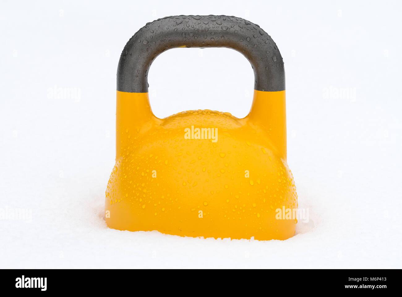 Poids kettlebell formation jaune dans la neige. Utilisation potentielle comme offseason / winter concept de formation. Photo Stock