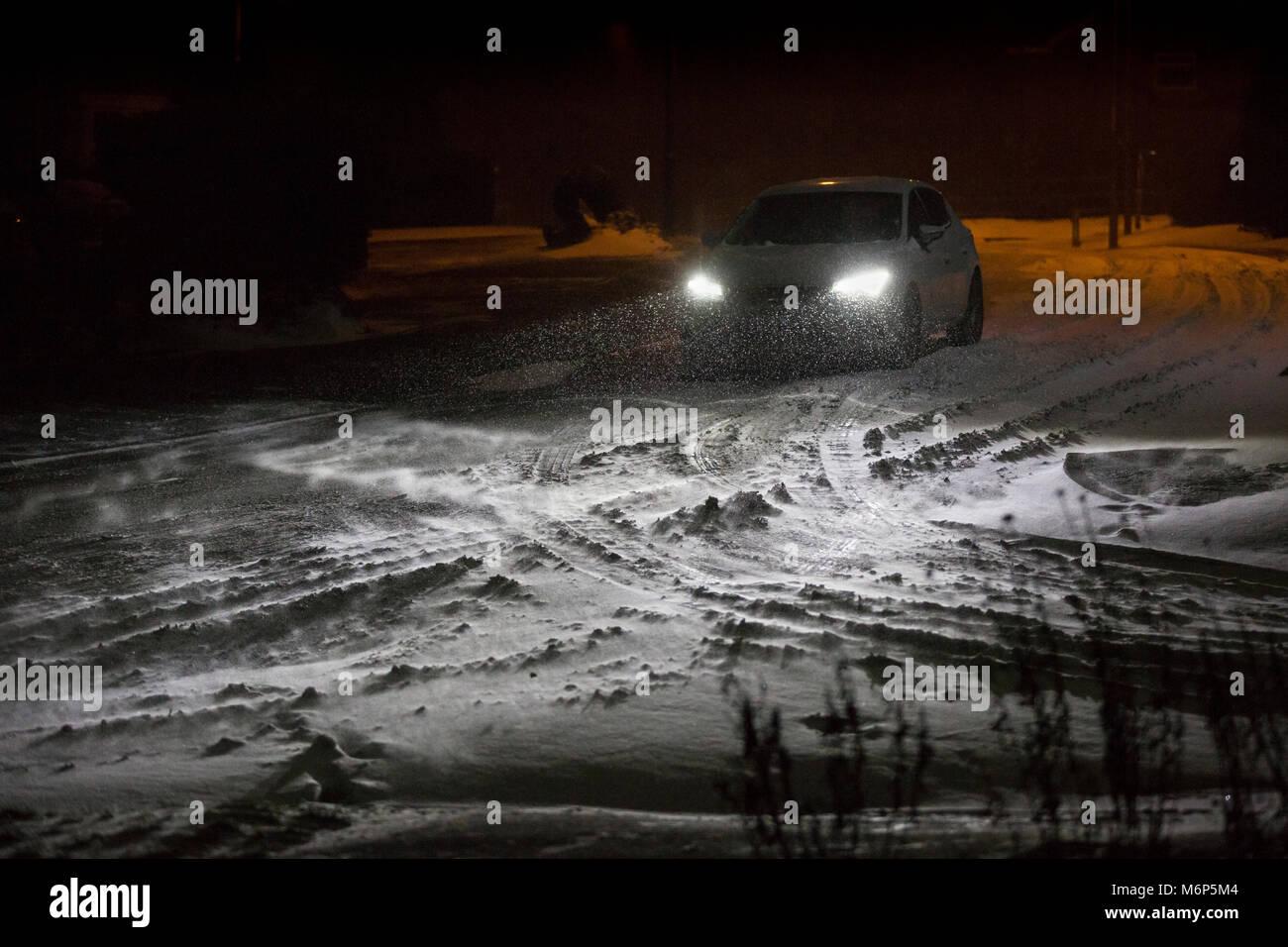 Une voiture roulant sur une route couverte de neige à Redditch, Royaume-Uni Banque D'Images