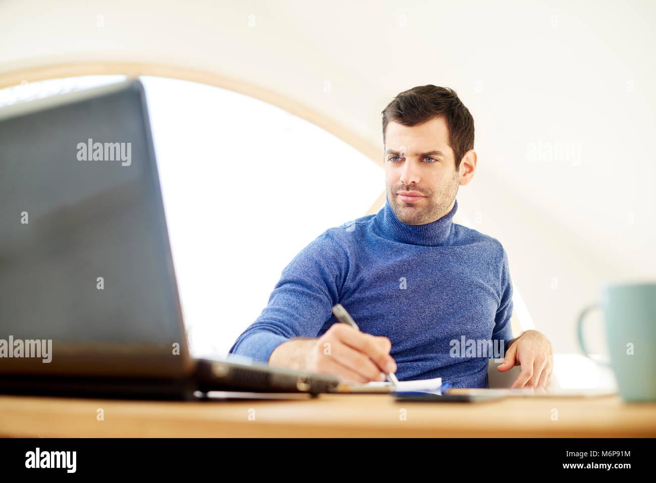 Portrait de jeune homme portant un chandail à col roulé et à thoughtul tout en travaillant uniquement Photo Stock