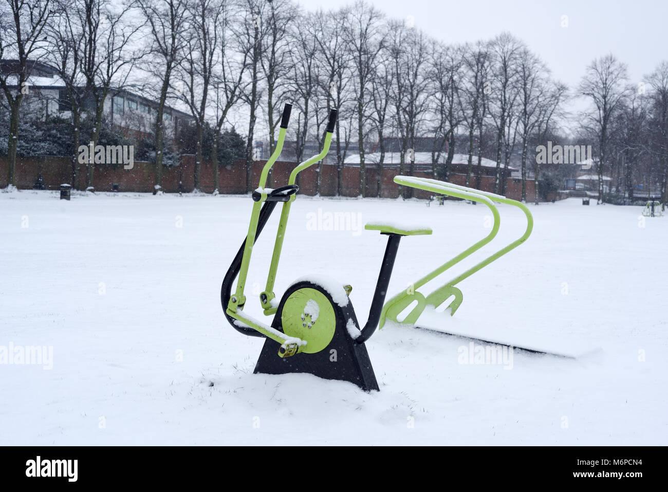 L'équipement d'exercice dans un parc public couvertes de neige,UK. Photo Stock