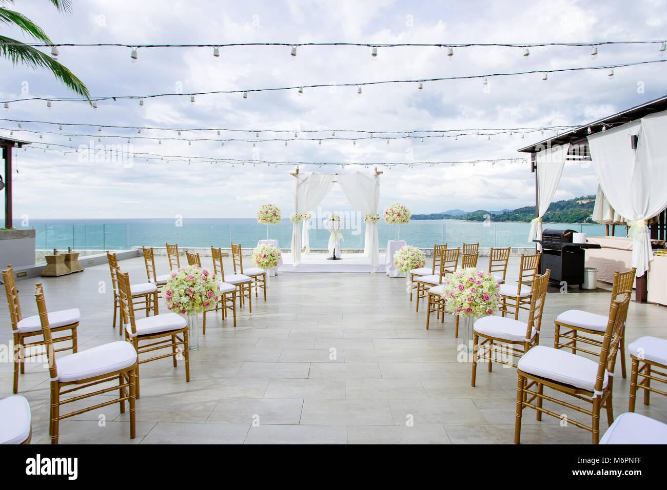 La salle de mariage sur la falaise, l\u0027or blanc thème des chaises pour  l\u0027invité, la vue panoramique sur l\u0027océan au coucher du soleil