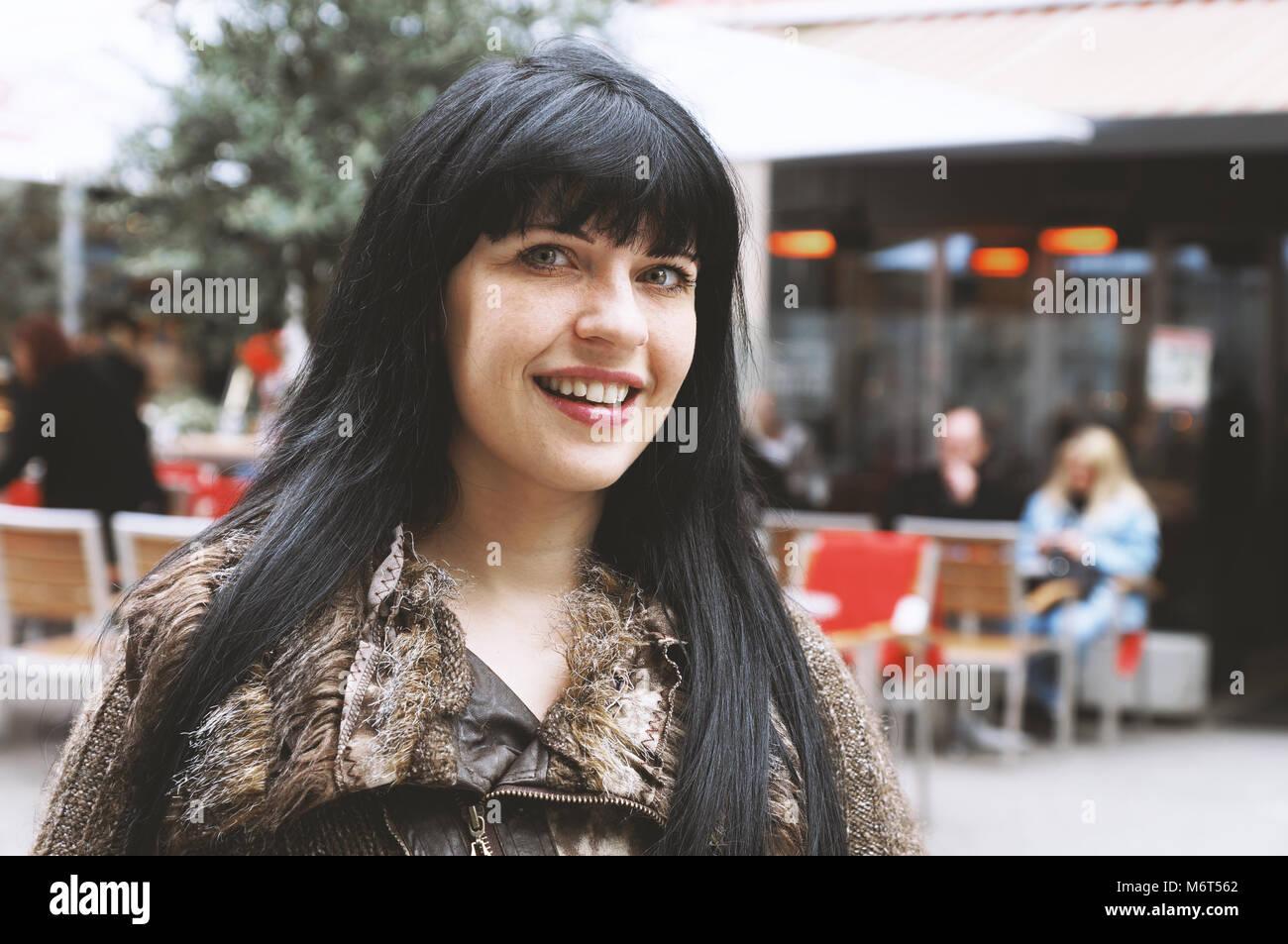 Jeune femme dans la rue piétonne du centre-ville en face d'un café en plein air Banque D'Images