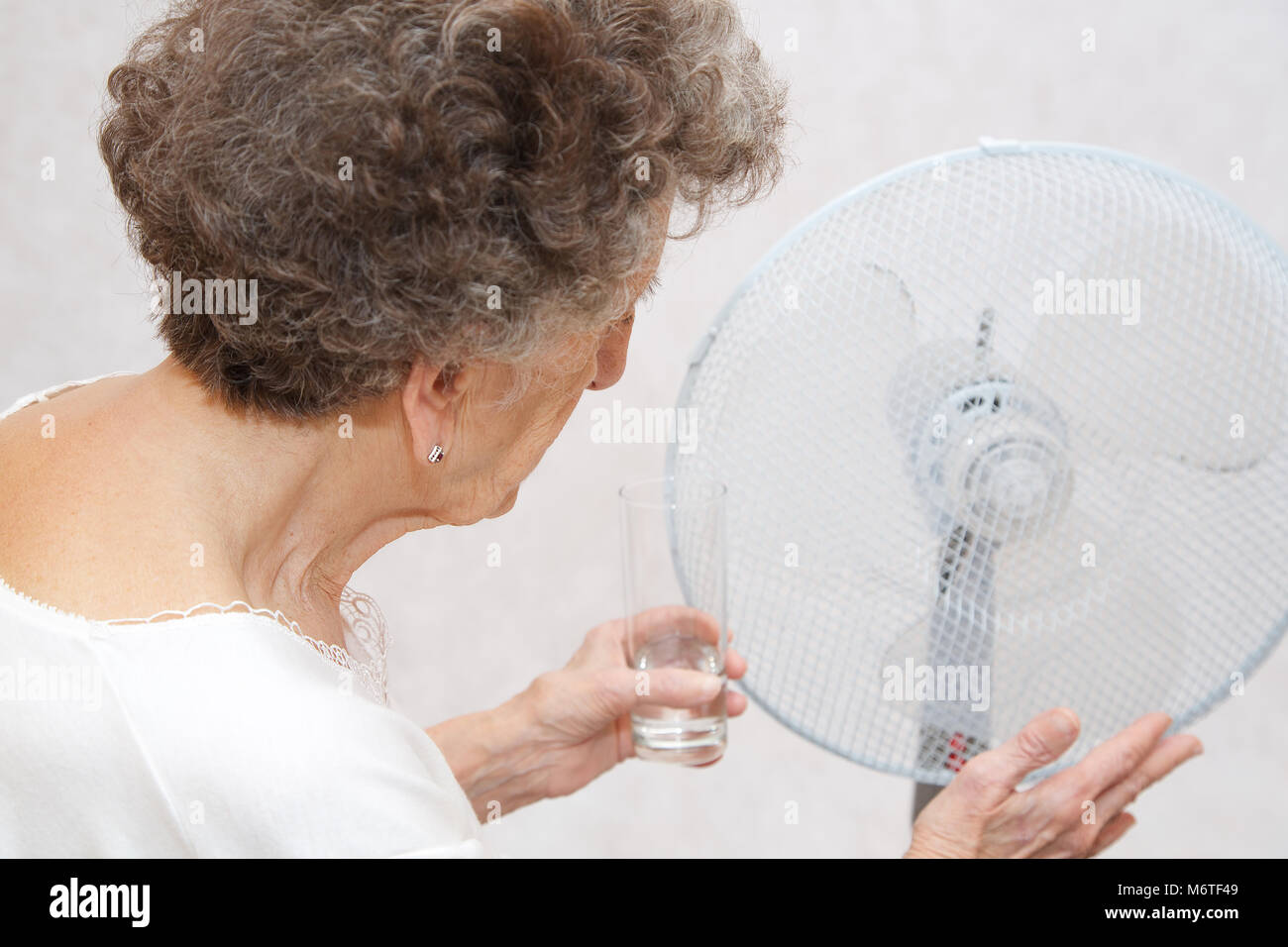 Hauts femme entre 70 et 80 ans reste proche des ventilateurs. Souffre de la chaleur Photo Stock