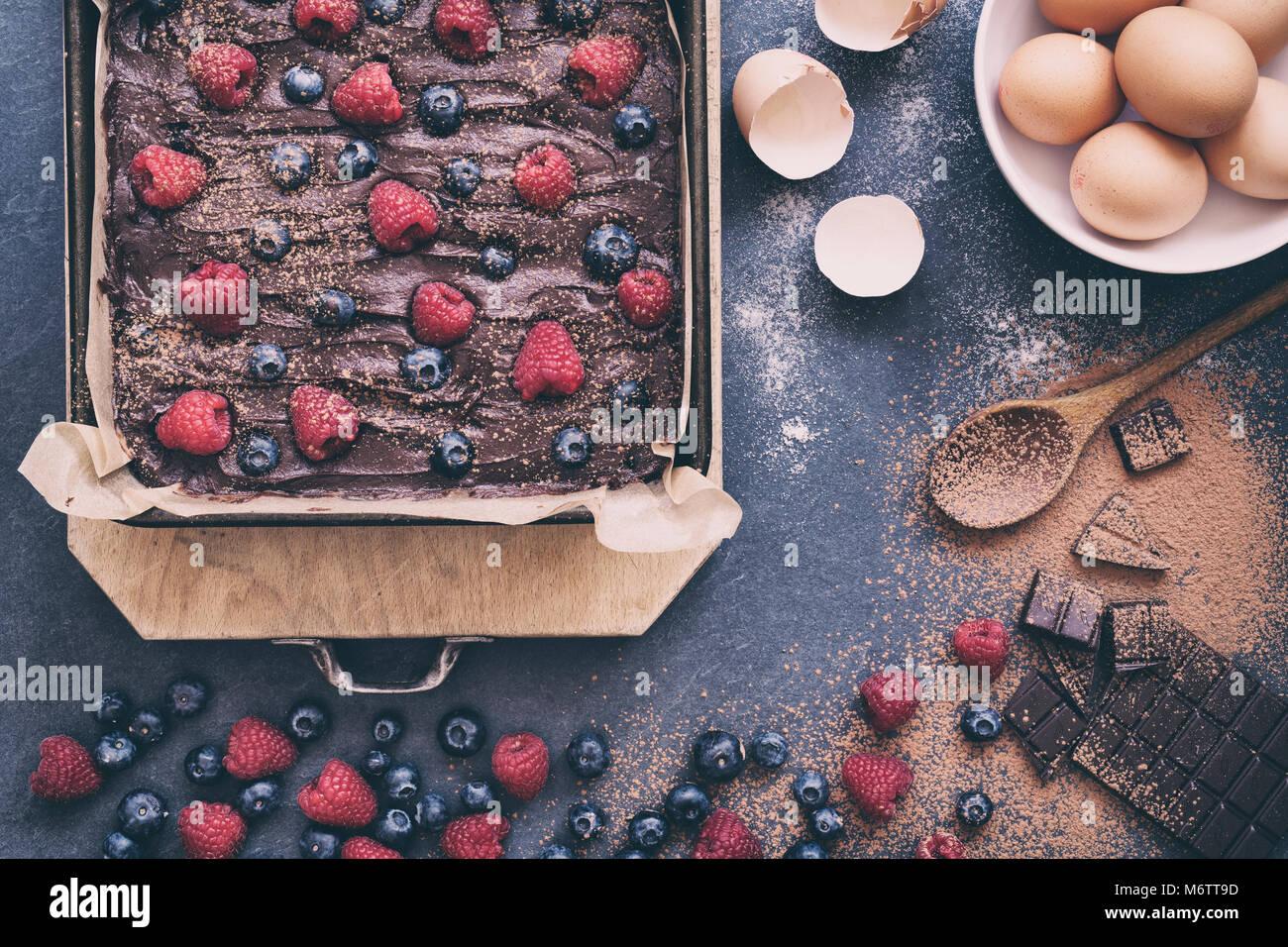 Des matières chocolat-framboise et bleuet mélange brownie dans une plaque à pâtisserie avec Photo Stock