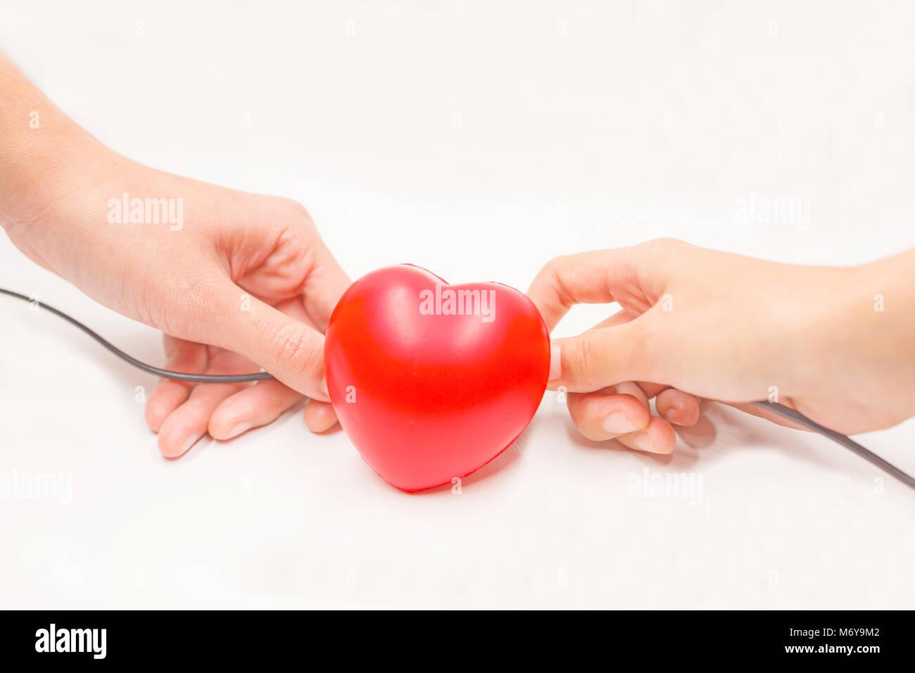 Les câbles de chargement avec les mains pour aider à la récupération du cœur sur fond blanc. Photo Stock
