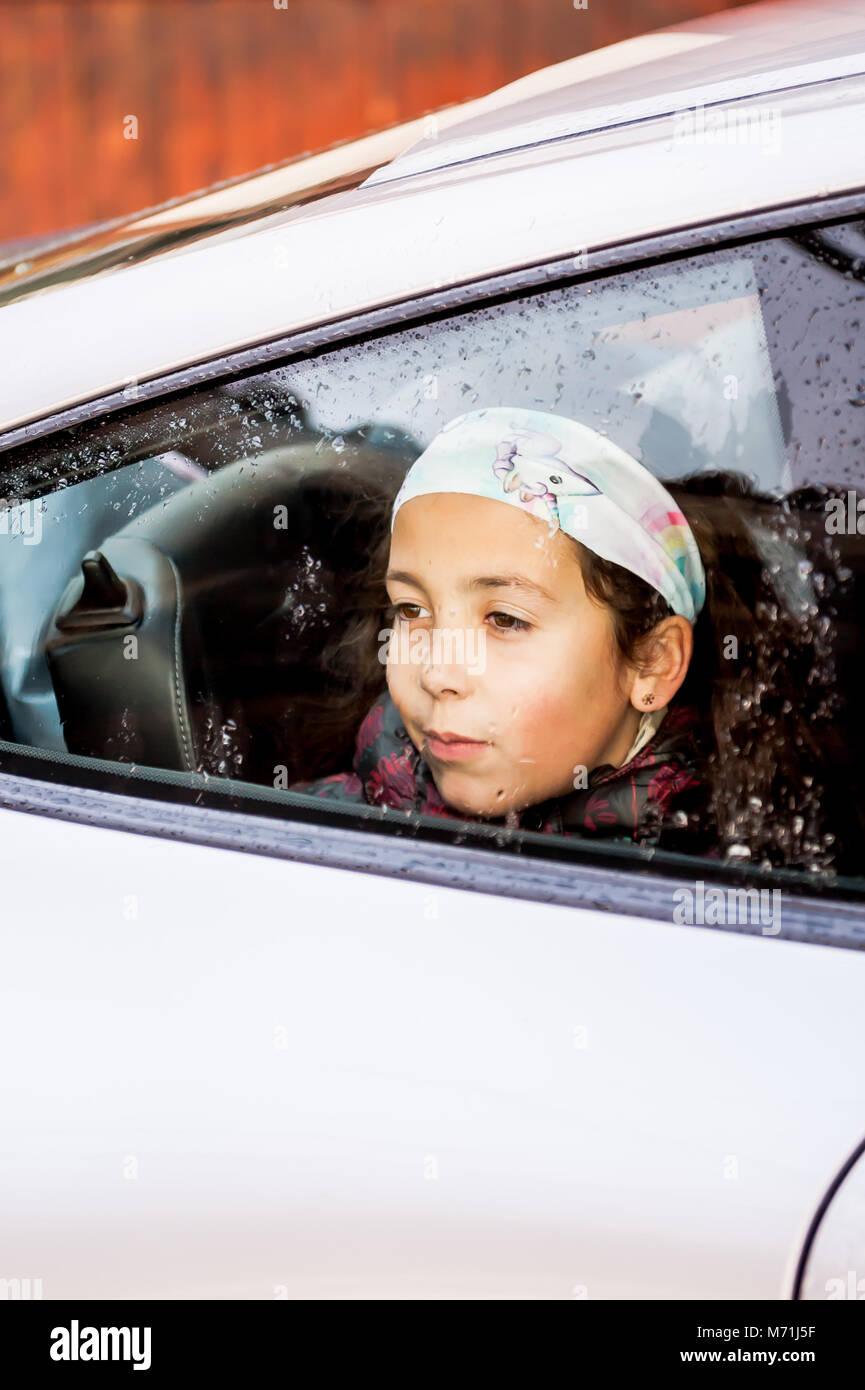 b5b0d2bf7f51 Jeune fille portant un foulard, assis à l arrière de la Porsche 911 avec  des gouttes de pluie sur la fenêtre. En corse en Décembre.