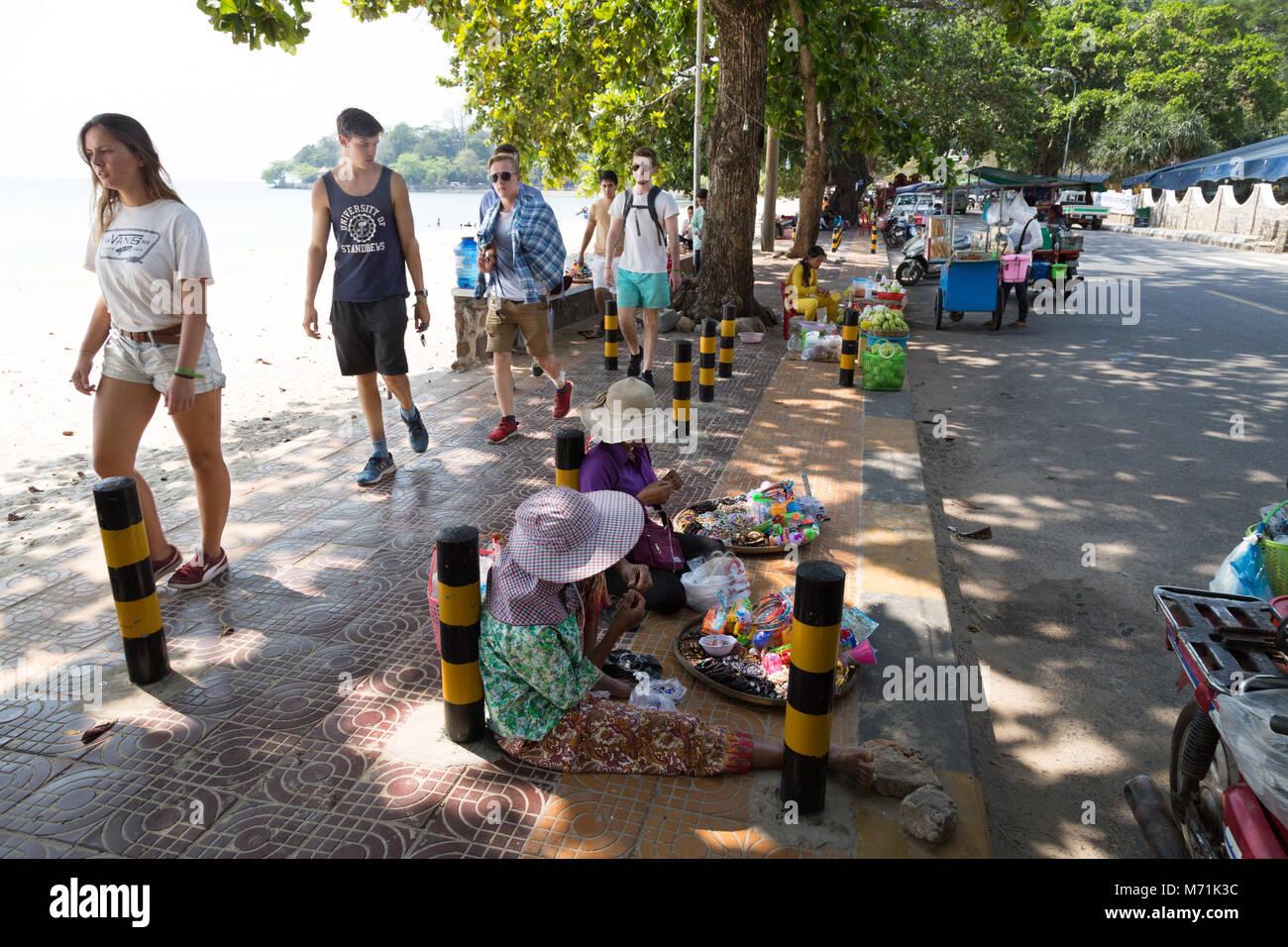 Les touristes de l'ouest en passant devant les stands, la plage de Kep, Kep, au Cambodge, en Asie du sud-est Photo Stock
