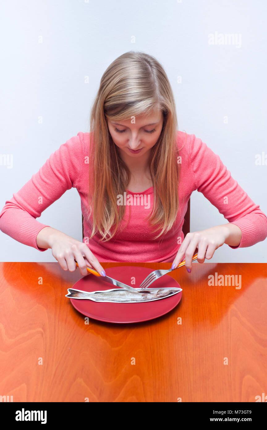 Jeune femme blonde fake de manger un poisson en carton, drôle l'inscription du concept pour l'alimentation, Photo Stock