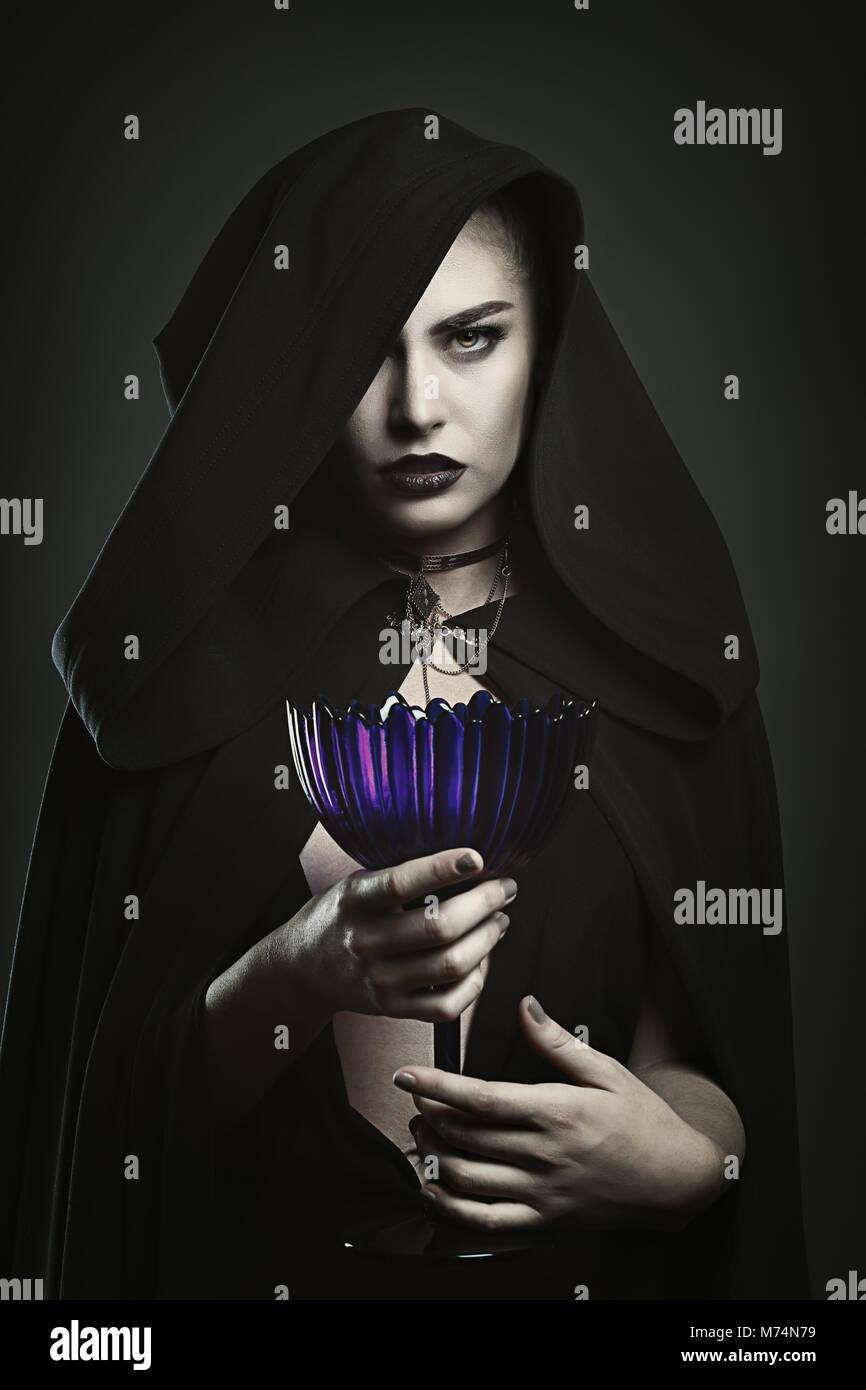 Belle vampire tenant une tasse. Rituel de sang Photo Stock