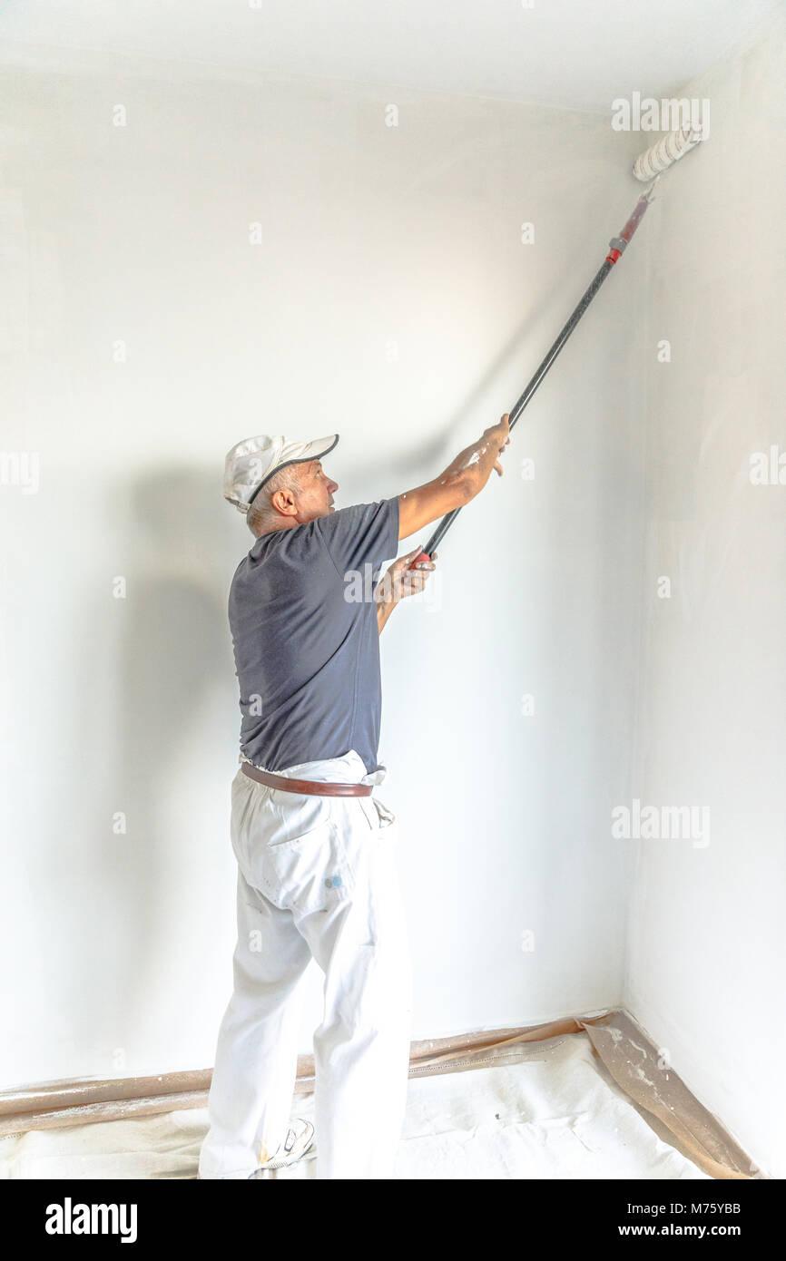 Man Peindre Un Mur Blanc Avec Rouleau à Peindre Dans La