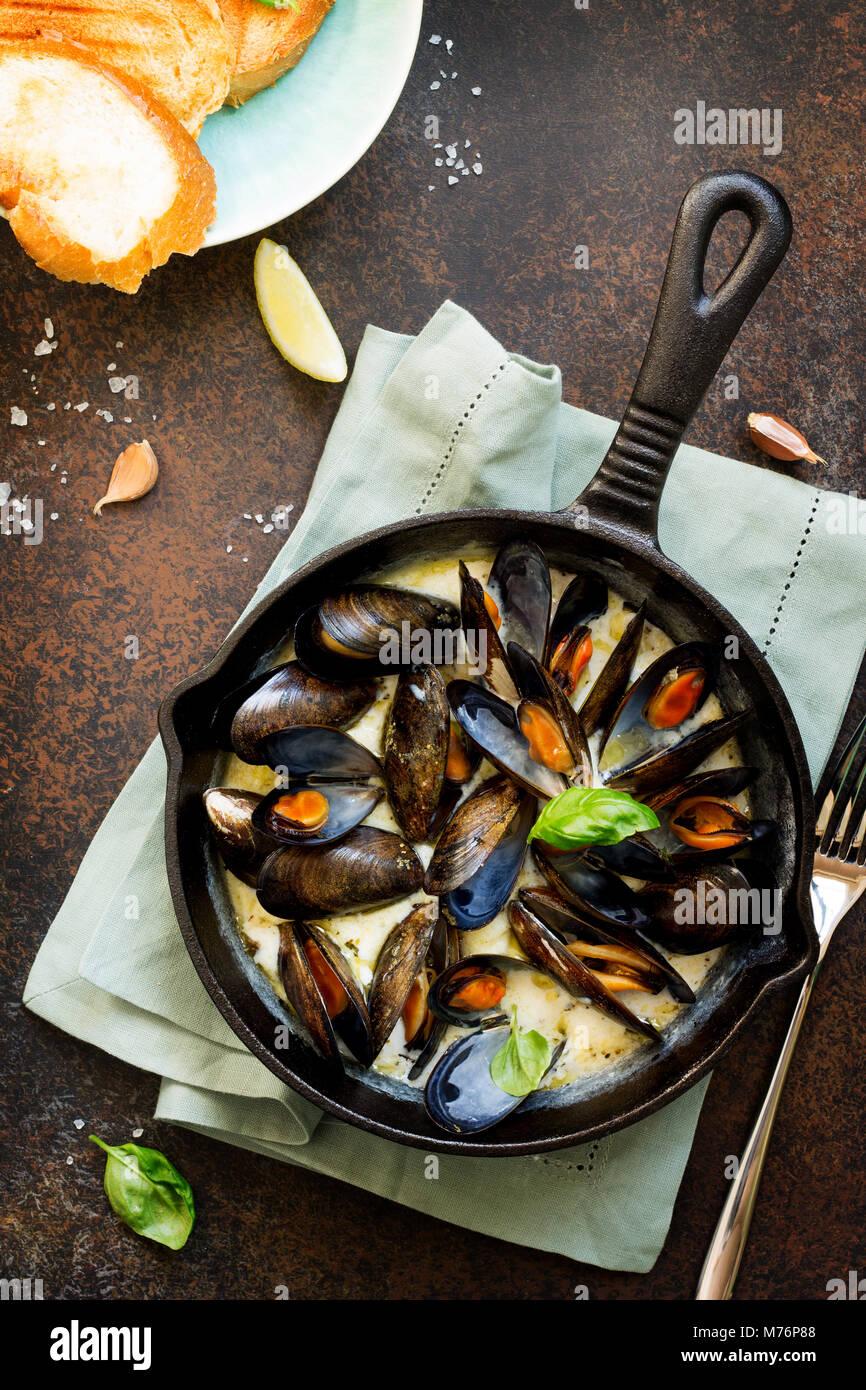 Les moules cuites dans une sauce de vin blanc, servi avec pain grillé et citron. La cuisine gastronomique italienne. Banque D'Images