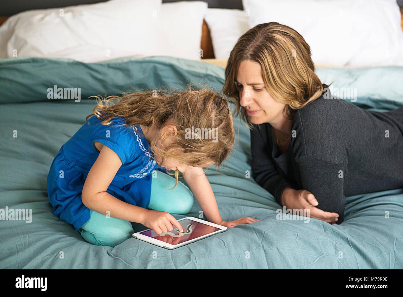 Une femme en regardant sa fille apprendre à écrire à l'aide d'un ipad mini. Banque D'Images