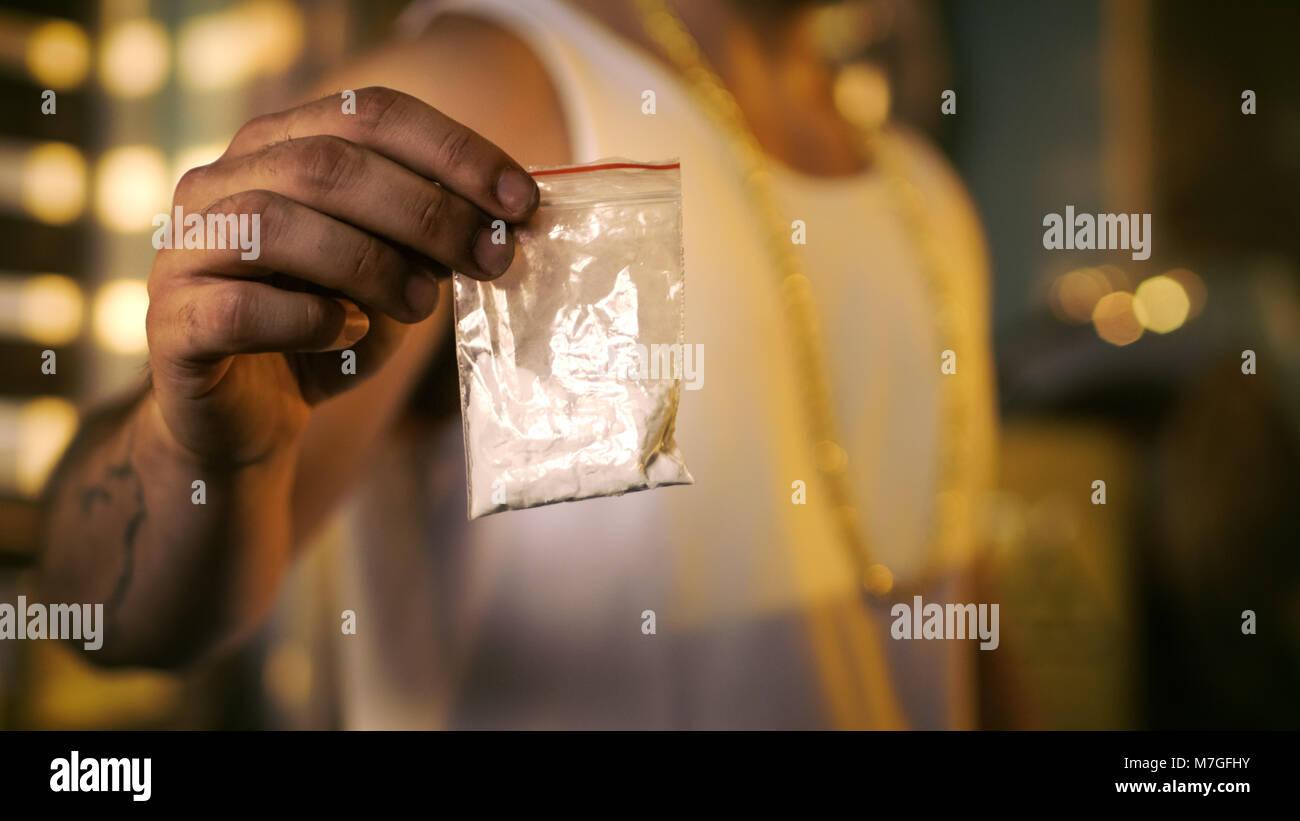 Le trafiquant de drogue brutale portant des T-Shirt et est titulaire d'une chaîne en or et de l'échantillon Photo Stock