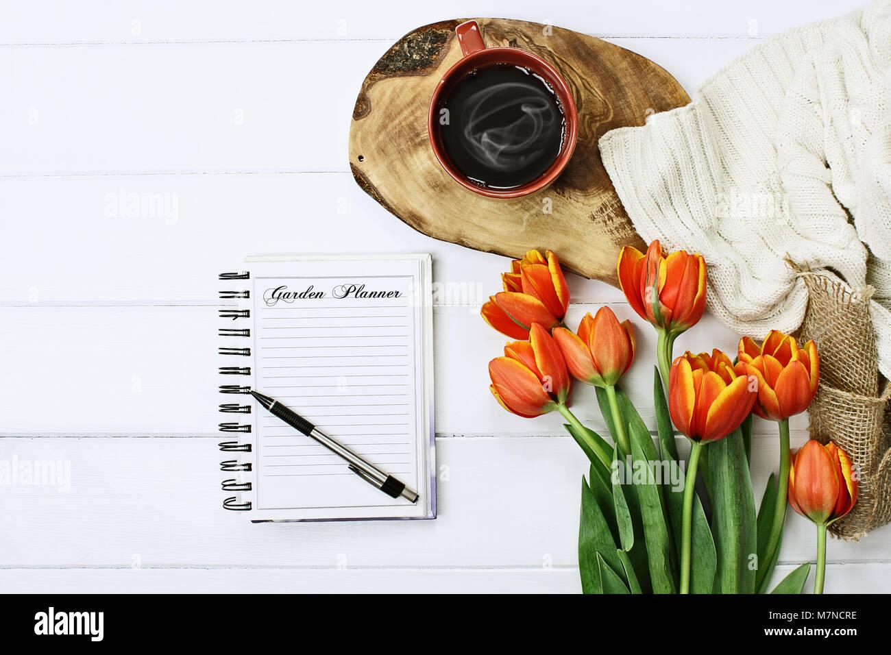 Passage tiré d'un journal de jardin portable avec stylo, de café et d'un bouquet de tulipes orange et jaune sur Banque D'Images