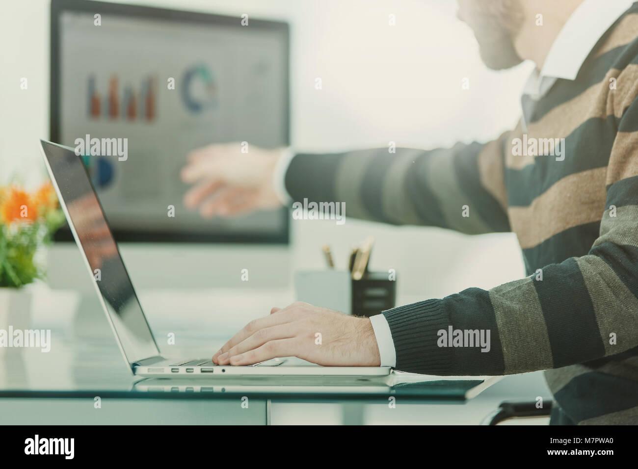 Spécialiste des finances travaille sur un ordinateur portable avec les cartes et plans de commercialisation Photo Stock