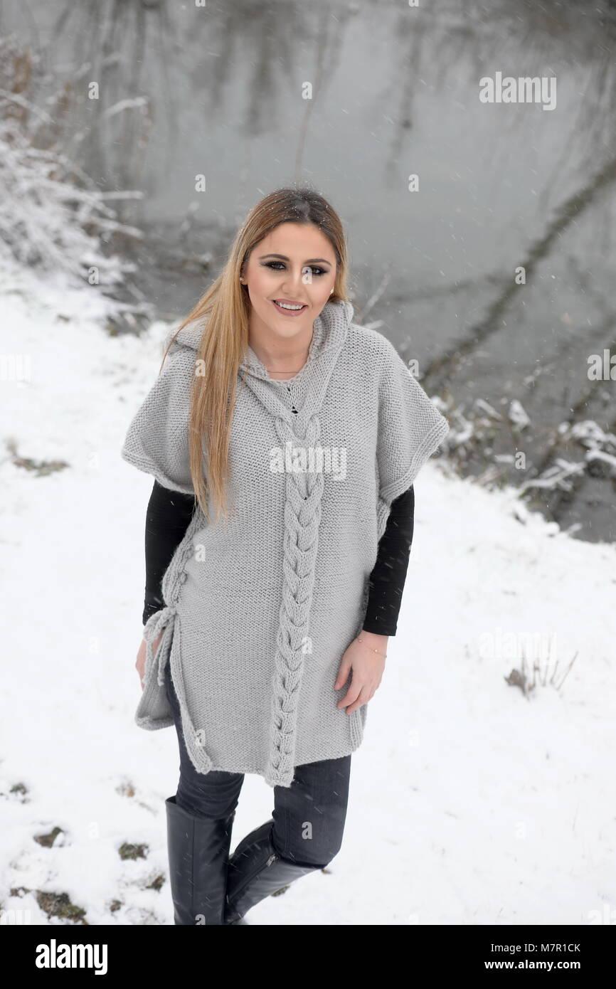 Belle jeune fille vêtue d'un pull tricoté à la main de longues manches courtes Photo Stock