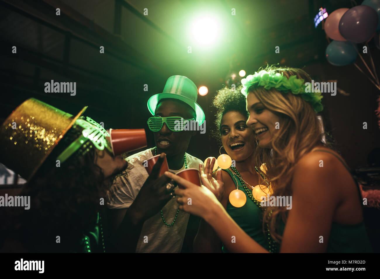 Groupe de multi-ethnic friends having fun at bar. Sourire les hommes et les femmes à faire la fête et célébrer le Jour de la Saint Patrick en discothèque. Banque D'Images