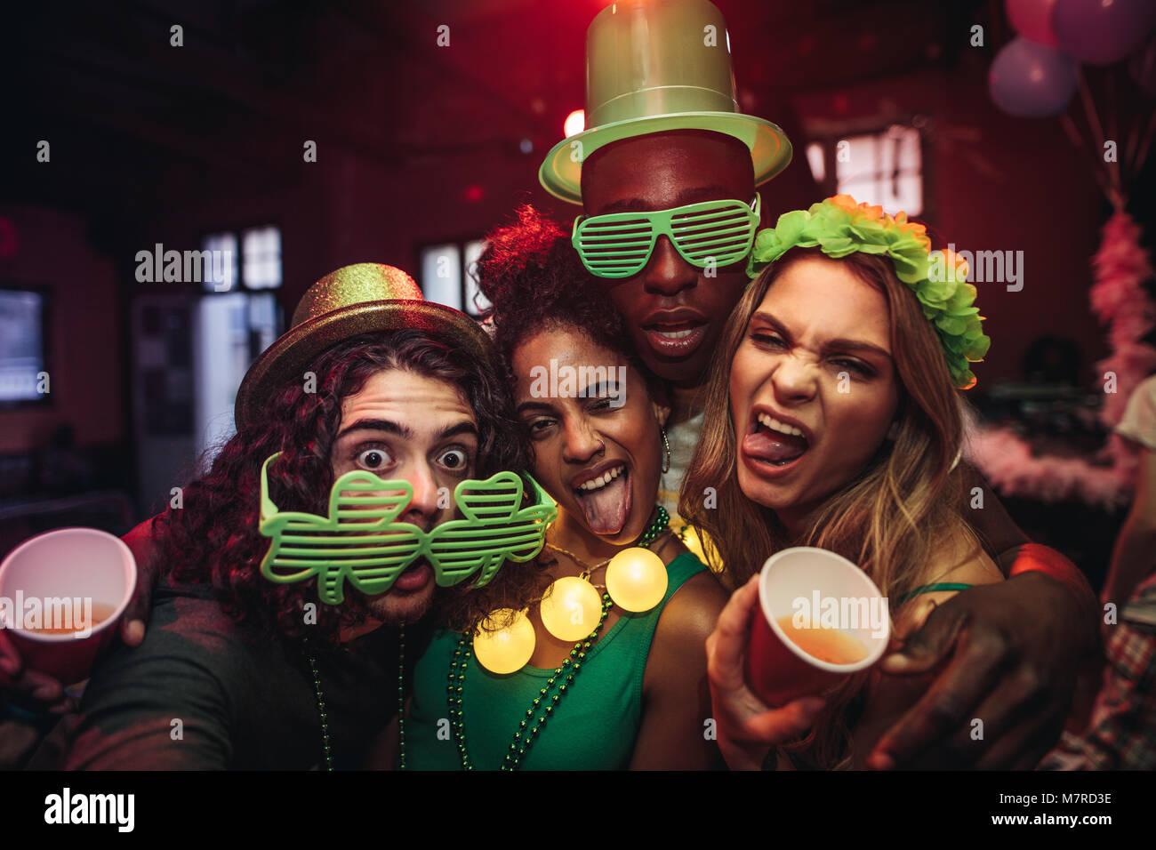 Crazy jeunes amis profitant d'une partie au pub. Les hommes et les femmes dans le trèfle vert partie lunettes Photo Stock
