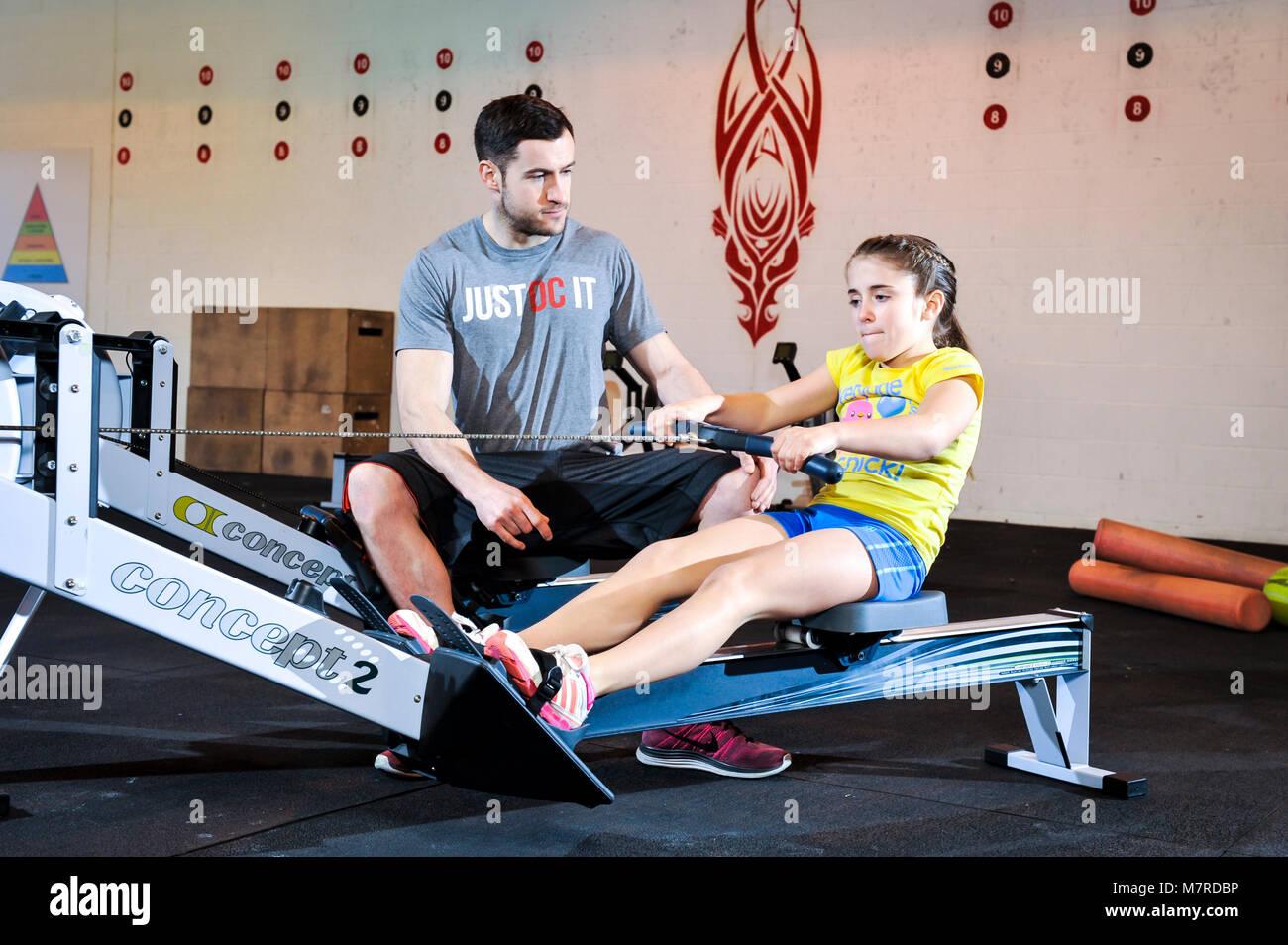 Une jeune fille a donné une leçon sur un rameur dans une salle de sport. Photo Stock