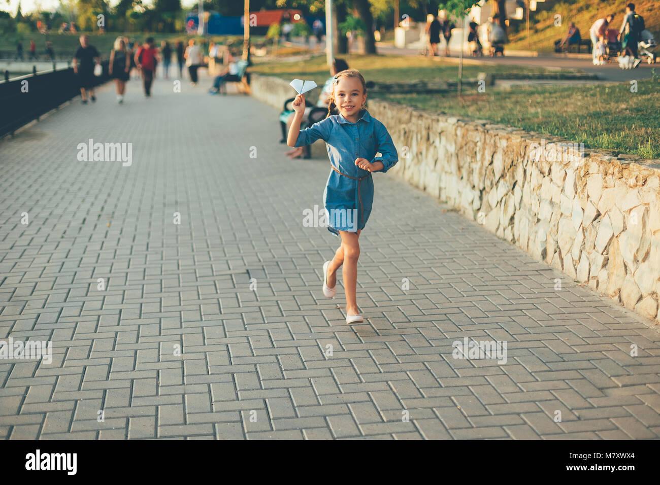 Enfant Jouer, courir avec toy avion en papier dans le parc, sur pavage gris près du lac en robe en jean. Smiling Photo Stock