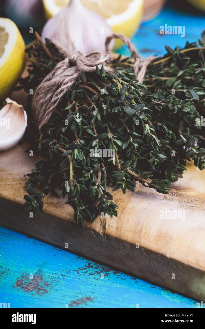 Bouquet de thym, de citrons frais et l'ail sur planche à découper en bois. Les ingrédients d'une Photo Stock