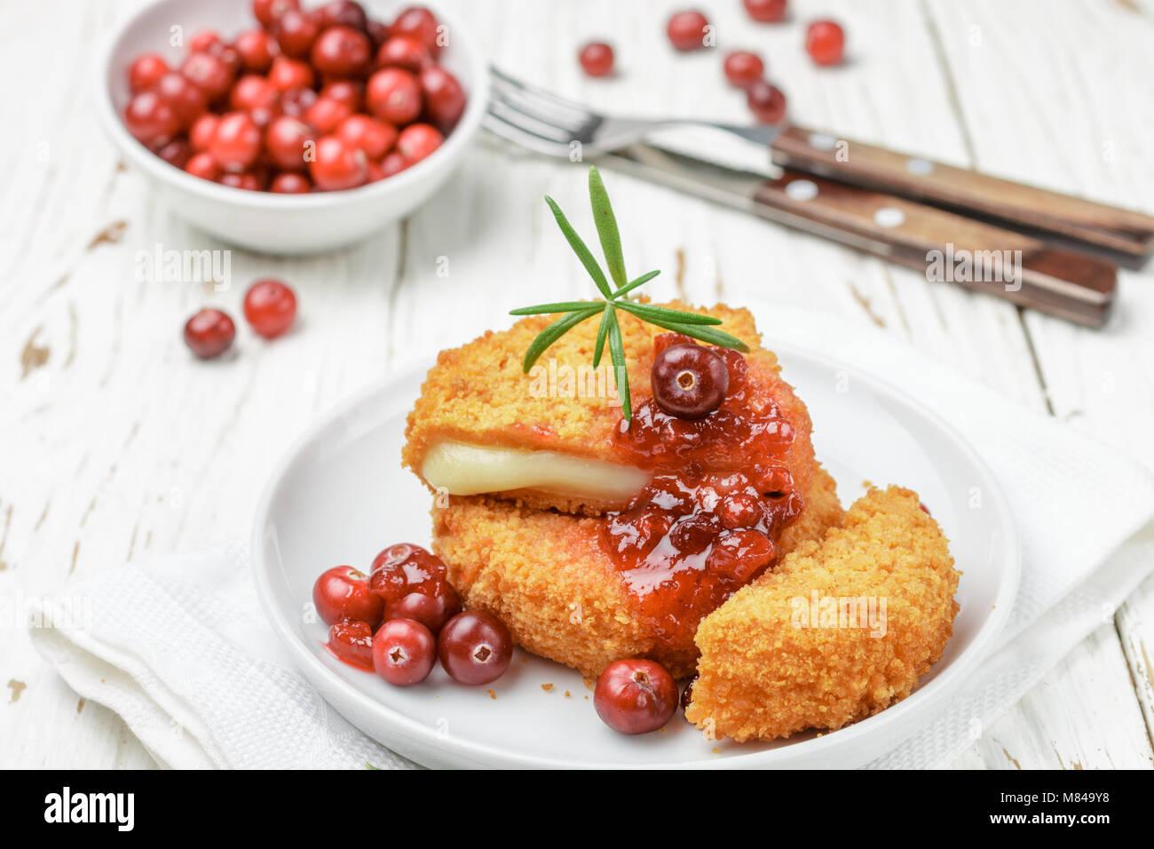 Camembert pané cuit au four (brie) avec les baies fraîches et sauce aux canneberges au romarin sur un Photo Stock