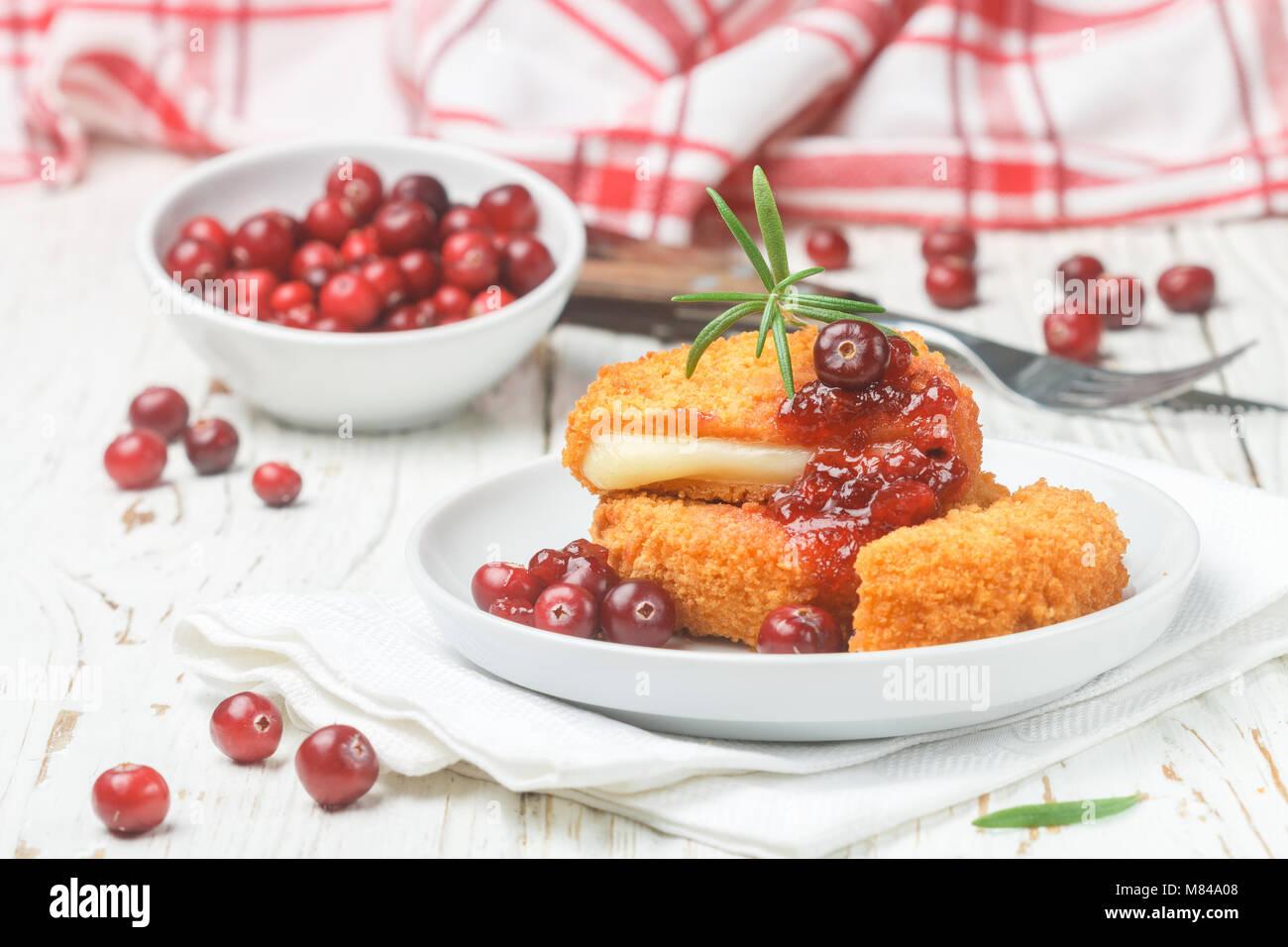 Camembert au four (brie) avec les baies fraîches et sauce aux canneberges au romarin sur une plaque blanche. Photo Stock